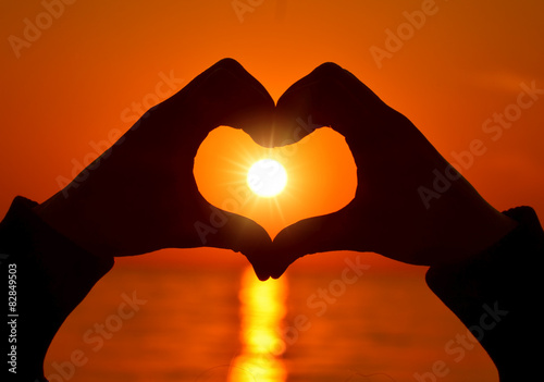 Romantic Heart Shape with hands at sunset