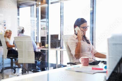 plakat Kobieta rozmawia za pomocą telefonu przy biurku w biurze