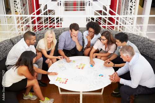 Fotografía  Group of work colleagues having meeting in an office lobby