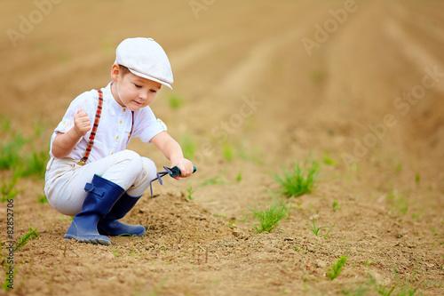 Staande foto Afrika cute little farmer working with spud on spring field