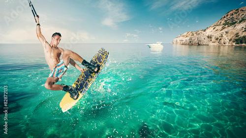 Wakeboarder making tricks on sea. Wakeboarding on beach.