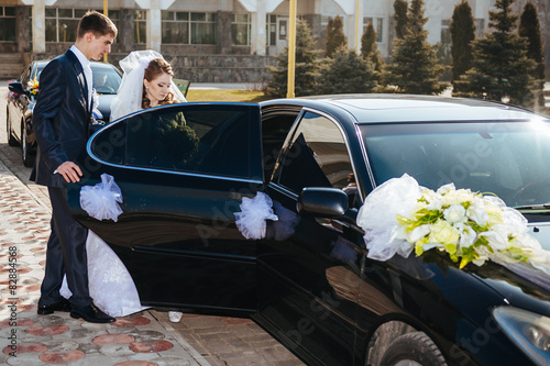Bride and groom kissing in limousine on wedding-day. Poster