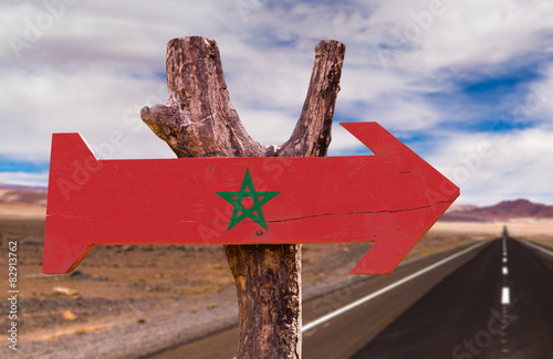 Tuinposter Marokko Marocco Flag wooden sign with desert road background
