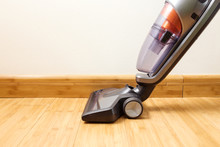 Cordless Vertical Vacuum Cleaner Cleaning Parquet Floor.