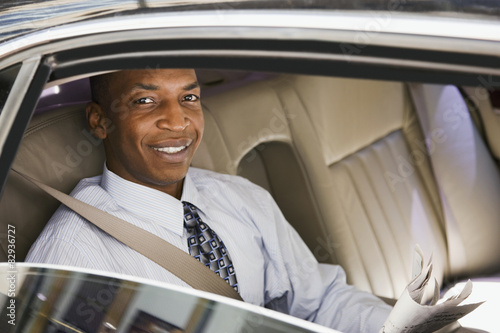African businessman riding in back seat of car Poster