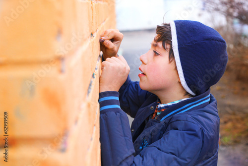 preteen handsome boy try himself as a graffiti artist on the yel Poster