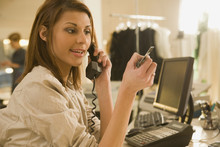 Mixed Race Woman Holding Credit Card On Telephone In Shop