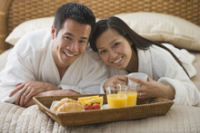 Asian Couple Eating Breakfast In Bed