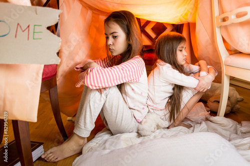 Two resentful sisters sitting on floor at bedroom back to back Wallpaper Mural