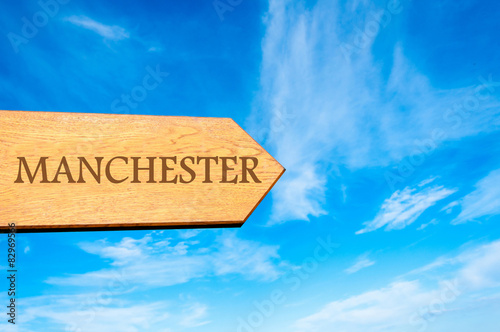 Wooden arrow sign pointing destination MANCHESTER, ENGLAND