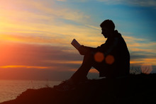 Silhouette Of A Man Sitting On Breakwater In Evening Near Sea, R