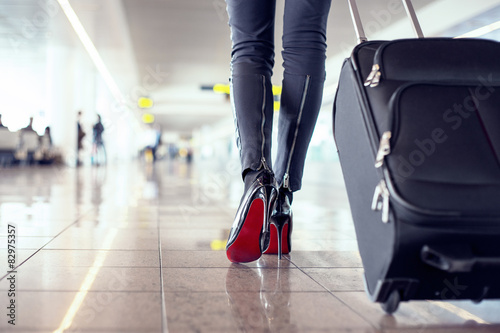 Photo  Woman walking in airport with hand luggage suitcase