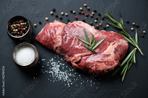 Fotografering  Raw ribeye steak with seasonings, close-up, studio shot