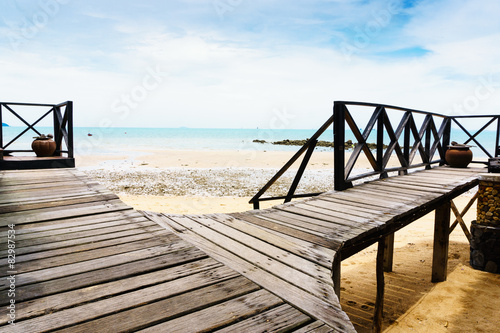 wooden walkway on beach with ocean view in background