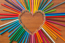 Colored Pencils Formed Into A Heart Shape On A Wooden Table