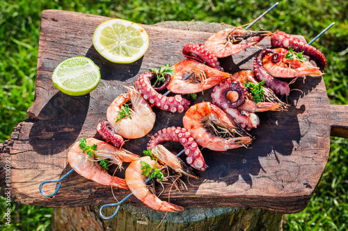 Poster Coquillage Tasty skewers of seafood with lemon and parsley in garden