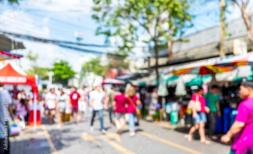 Fotomural Blurred background : people shopping at market fair in sunny day