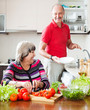 happy elderly man and mature woman doing chores