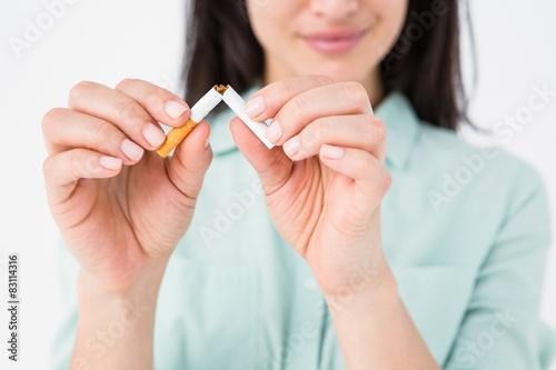 Fotografia, Obraz  Smiling woman snapping cigarette in half