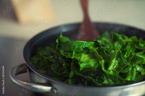 Poster Cuisine Vegetarian food concept. Fresh spinach cooking in metal pot.