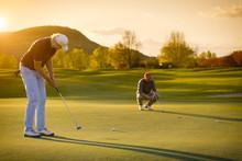 Two Senior Golf Player At Sunset.