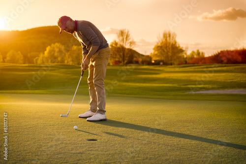 Deurstickers Golf Male golf player putting at sunset.