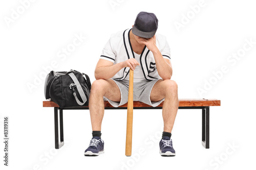 Photo  Sad young baseball player sitting on a bench