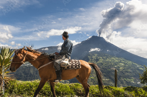 Unrecognizable farmer on a horse front of volcano Tungurahua