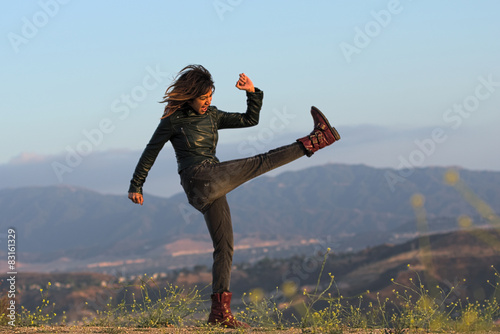 Fotografie, Obraz  Woman in leather jacket and boots kicking air
