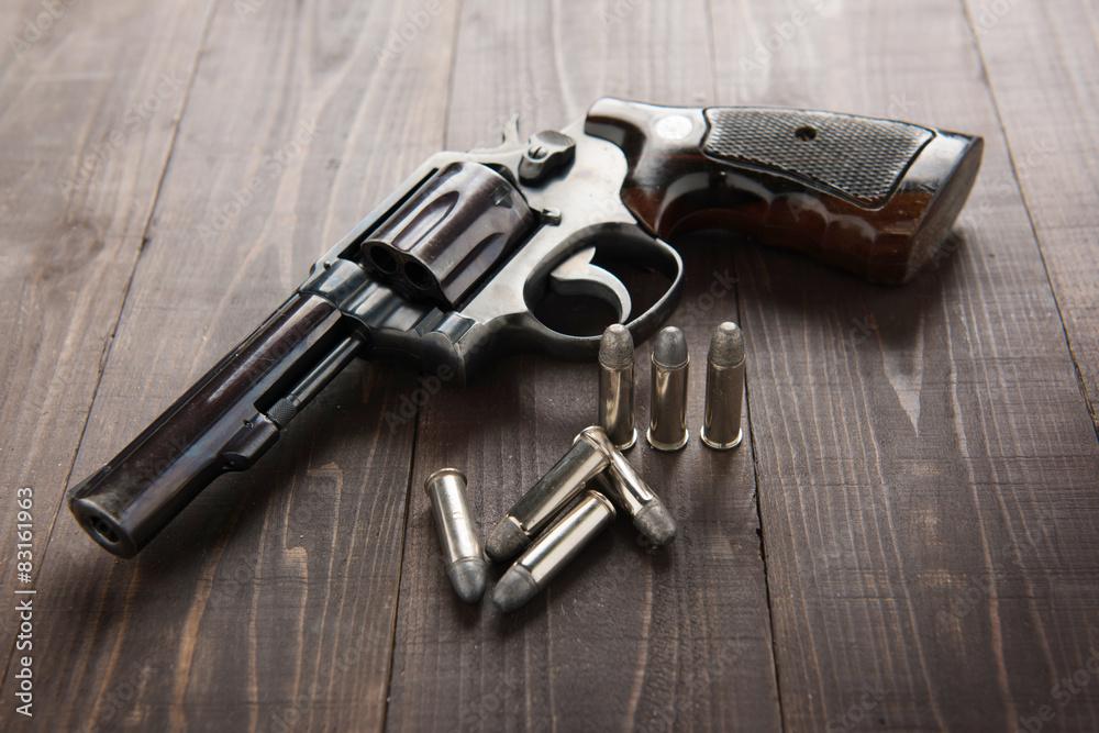 Fototapeta black revolver gun with bullets isolated on wooden background