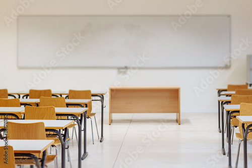 Desk and chairs in classroom Плакат