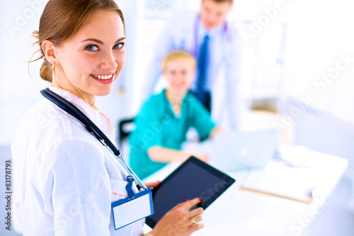 Young woman  doctor holding a tablet pc Poster