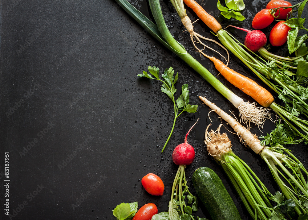 Young spring vegetables on black chalkboard from above. Background layout with free text space. Carrots, tomatoes, zucchini, leek, radish, celeriac, parsley and basil - fresh harvest from the garden.