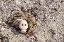 Head Of Children's Doll On The Beach Trash