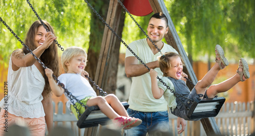 Parents with kids at swings