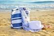 Hat, bag, sun glasses and flip flops on a sandy beach. Summer va