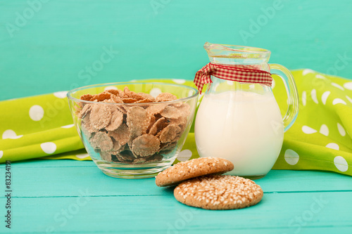 Fotografie, Tablou  Jug of milk with muesli and cookies on blue wooden kitchen