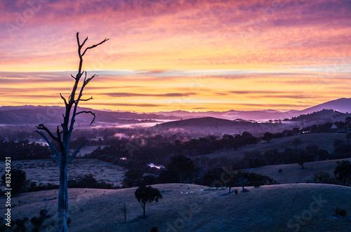 plakat Kolorowe wschód słońca nad zamglonym dolinie w Australii