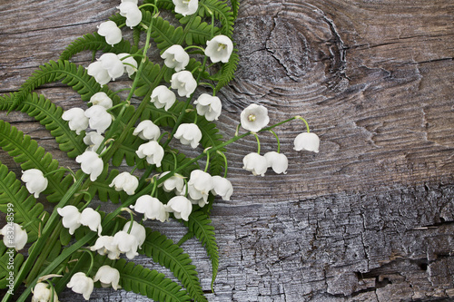 Poster Muguet de mai Lilies of the valley and fern leaf on a wooden background