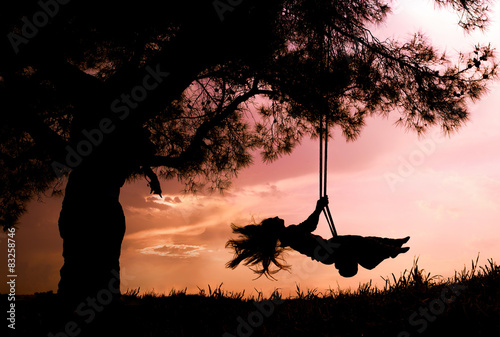 Fotografia  silhouette of happy young woman on a swing with sunset