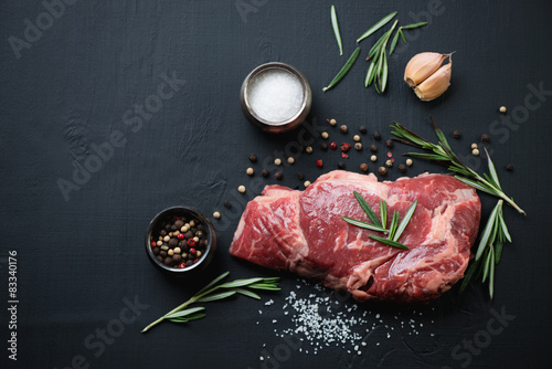 Fotografering  Above view of raw ribeye steak with spices over black background