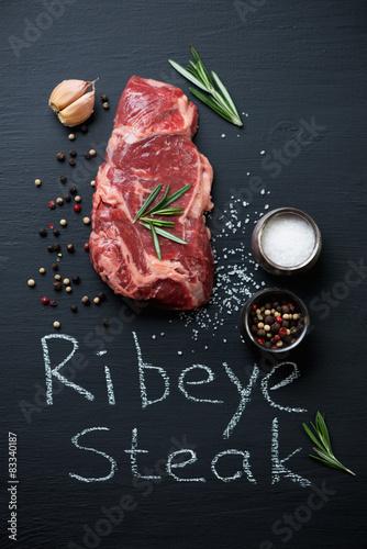 Photo  Fresh ribeye beef steak with seasonings, above view, studio shot
