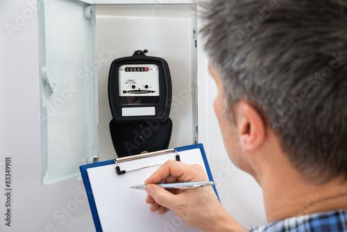 Fotografie, Obraz  Technician Taking Reading Of Electric Meter
