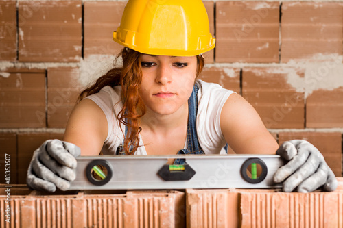 Fotografia, Obraz  Woman Bricklayer Holding a Spirit Level on a Brick Wall