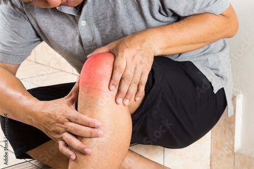 Fotografiet  Matured man suffering from painful knee joint seated on steps