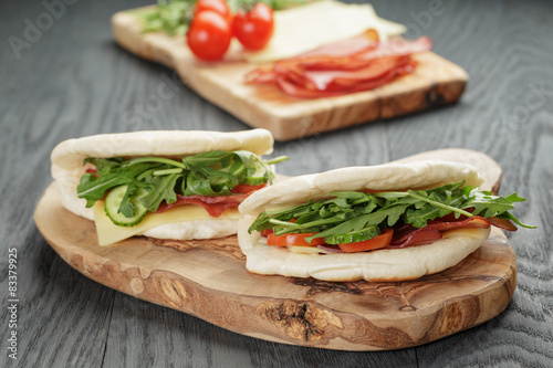 Foto op Canvas Snack rustic sandwiches with ham arugula and tomatoes in pita bread