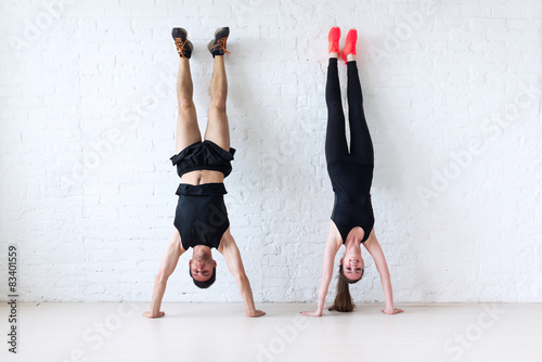 sportsmen woman and man doing a handstand against wall concept Canvas Print