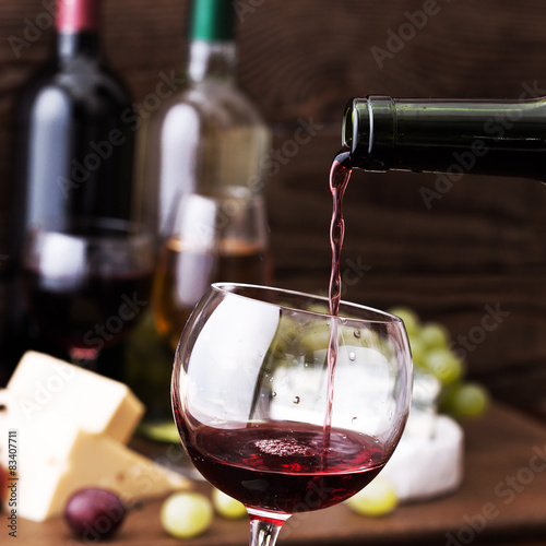 Red wine pouring into glass, close-up. Poster