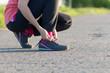 Girl tying shoelaces shoes sitting on the asphalt road
