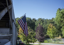 American Flag Hanging From A Horse Stable.